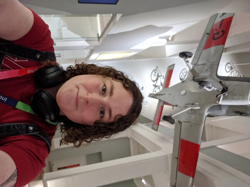 A girl with curly hair (who is quite tall) with a red t-shirt with the Armakuni logo on, headphones around her neck and a pinafore dress on, standing under a plane suspended from the ceiling at Agile Scotland at the National Museum of Scotland