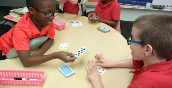 Video thumbnail: two young students engaging in an unplugged programming activity using playing cards